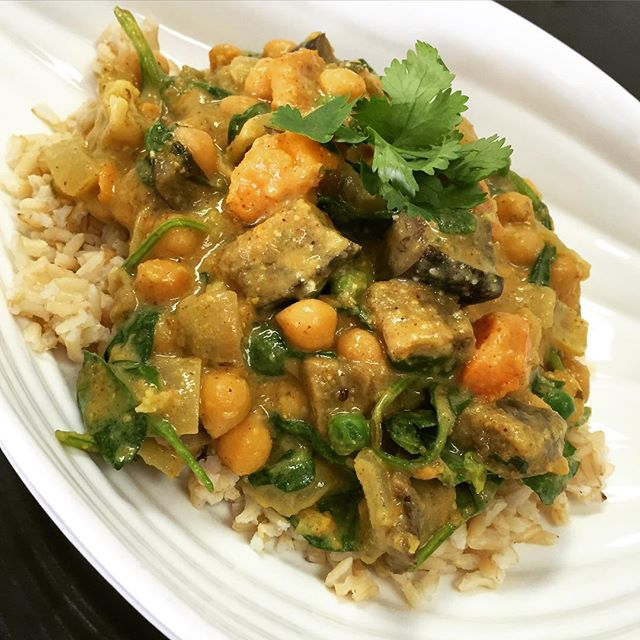 South Indian chickpea curry with spinach, eggplant, cauliflower, green peas and sweet potato simmered in an almond coconut spiced broth served over brown rice #glutenfree #vegan #soyfree #wholegrain #wheatfree #veganindian #glutenfreeindian #southindiancurry
