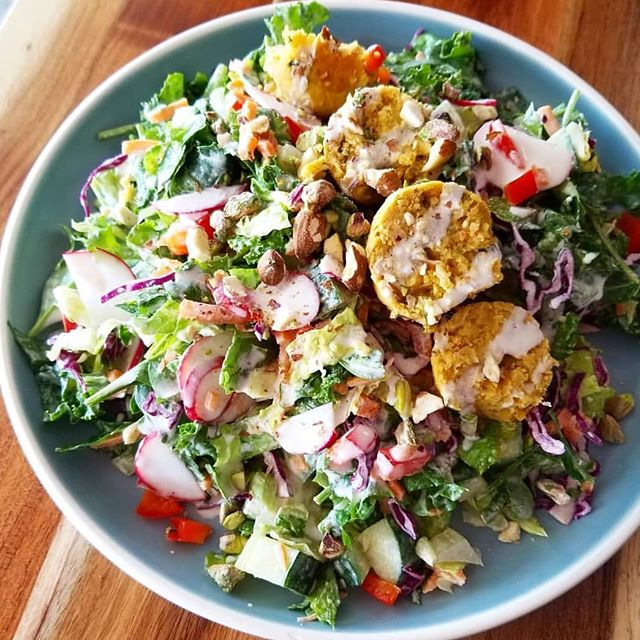 The Middle Eastern Salad bowl with sweet potato falafel, romaine, kale, spinach, bell peppers, carrots, cabbage and radish topped with currant raisins, pistachios and almonds covered with a lemon tahini dressing #glutenfree #vegan #plantbasedgoodness #vegandishes #saladmeals
